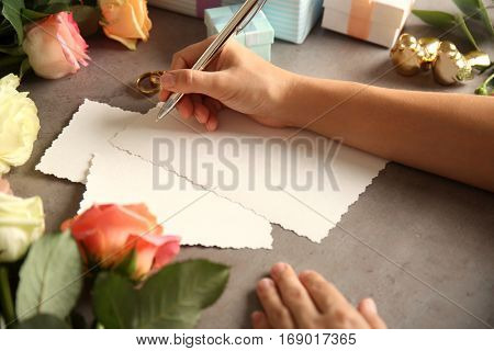 Female hands writing wedding to do list on table