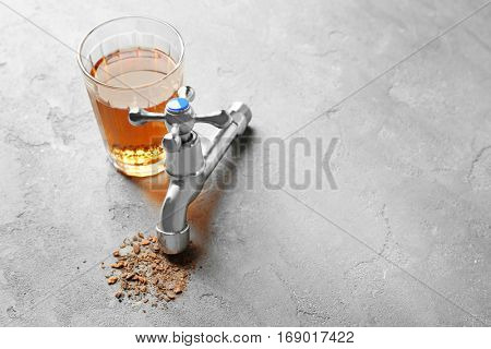 Faucet with glass of dirty water and rust flakes on gray textured background