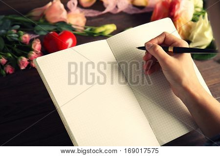 Female hand writing wedding to do list on table