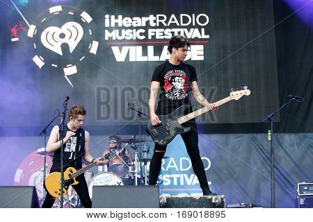 LAS VEGAS-SEP 20: (L-R) Luke Hemmings, Ashton Irwin and Calum Hood of 5 Seconds of Summer perform at 2014 iHeartRadio Music Festival at MGM Resorts Village on September 20, 2014 in Las Vegas, Nevada.