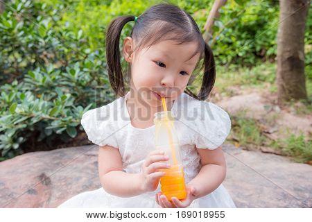 Little asian girl drinking orange juice from bottle