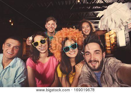 Soccer fans taking selfie in sport bar