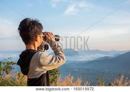Young asian boy using binocular to watch mist in forest