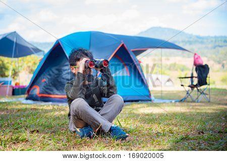Young asian boy looking through binocular in camping