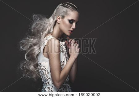 Beautiful girl in art dress with avant-garde hairstyles. Beauty the face. Photos shot in the studio.