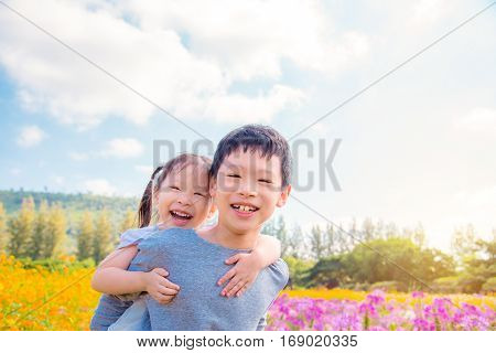 Young asian sibling happy at flower garden