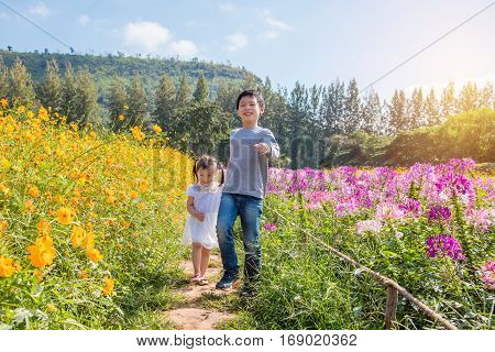 Young asian sibling running in flower garden