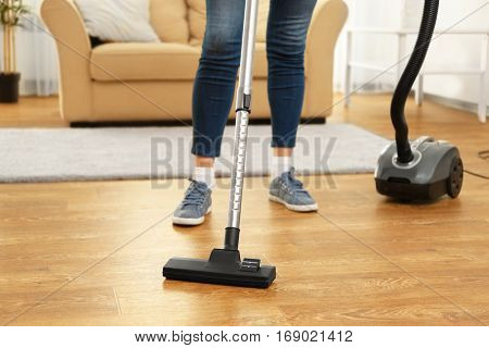 Cleaner hoovering floor in room