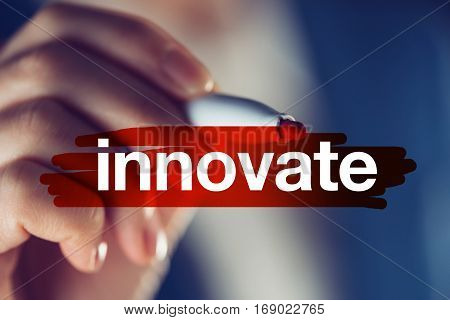 Innovate business concept businesswoman highlighting word with red marker pen