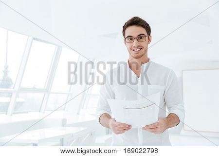 Picture of cheerful young man dressed in white shirt standing near big white window while holding documents.
