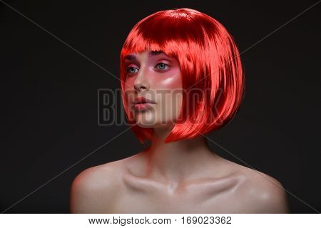 Beautiful young woman with glowing skin, fashion make-up and metallic nails in short red wig touching hair. Beauty shot on black background. Copy space.
