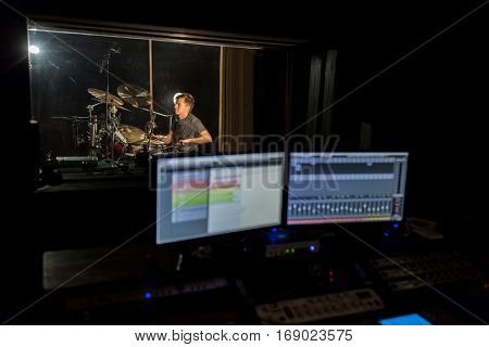 music, people and show business concept - sound mixing console with monitor screens and male musician playing drum kit at recording studio