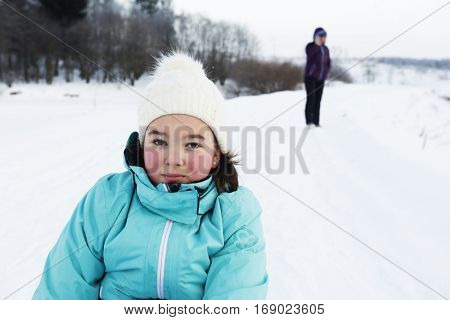 Girl teenager in winter clothes near  snow-covered forest. Her cheeks were red from cold.