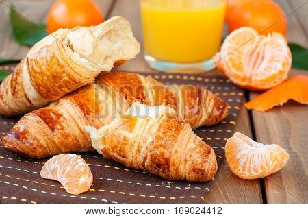 Fresh croissant and orange juice on wooden table horizontal