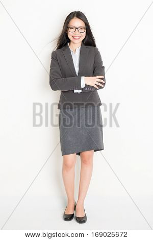 Portrait of young Asian female business people in formalwear smiling, full body standing on plain background.