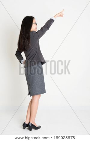 Rear view of Asian businesswoman in formalwear hand pointing away and smiling, full body standing on plain background.