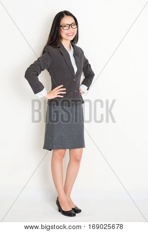 Portrait of Asian businesswoman in formalwear hand on waist and smiling, full body standing on plain background.