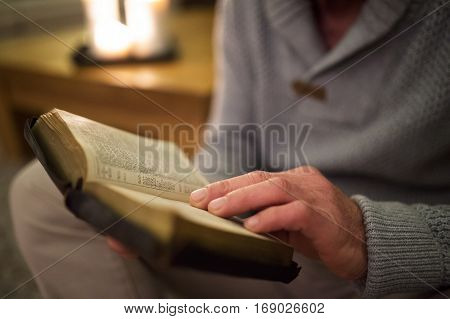 Unrecognizable senior man at home in his living room, sitting on the floor, reading Bible. Burning candles behind him.