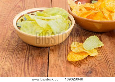 Potato chip flavored wasabi and paprika in two different ceramic bowls and separately beside closeup on an old wooden surface