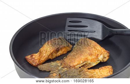 Fragment of an aluminium cast frying pan with ceramic non-stick coating with fried tail portion and other slices of carp and plastic spatula on a light background