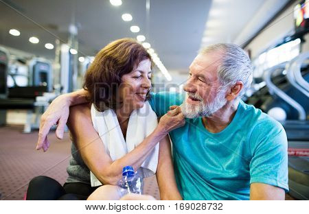 Beautiful fit senior couple in sports clothing in gym resting after working out, sitting in front of treadmills