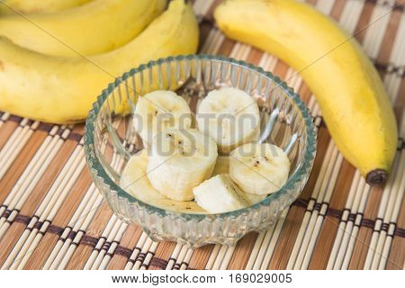 A banch of bananas and a sliced banana in a pot over a wood background.