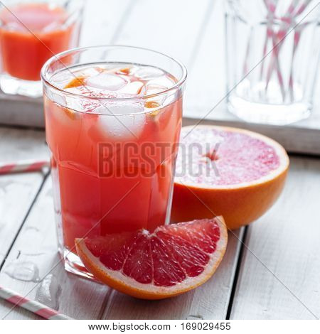 Cold juice with pink grapefruit and crushed ice on wooden table square image