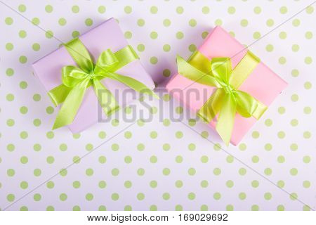 Two gift boxes with green bows on a polka dot background. Copy space.