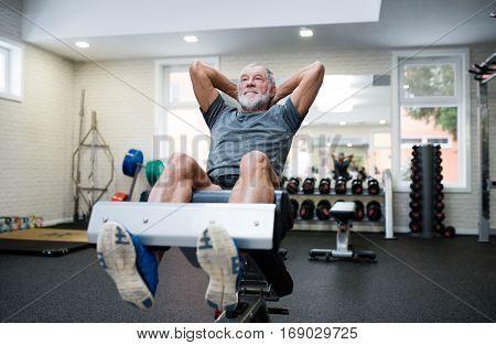 Fit senior man on a bench in gym in sports clothing working his abs, doing abdominal crunches.