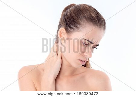 a young girl holds a hand behind the neck and lowered down her head isolated on white background