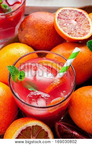 Close up of fresh delicious juice with red oranges on white wooden background selective focus