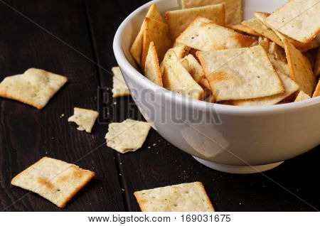 Biscuits salty crackers in bowl on wooden table horizontal selective focus