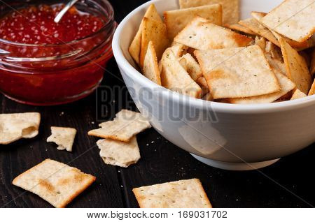 Close up of salty crackers in bowl and red caviar in background on wooden table selective focus