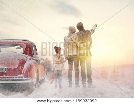 Toward adventure! Happy family relaxing and enjoying road trip. Mom, dad, child and vintage car on snowy winter nature background. Christmas holidays time.