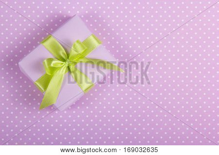 A small box with a bow on a polka dot background. Copy space.
