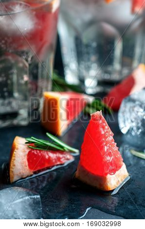 Close up of grapefruit ice and rosemary for cocktail dark stone background selective focus