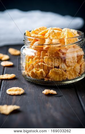 Close up of cornflackes in jar on dark wooden background selective focus vertical. Healthy food concept.