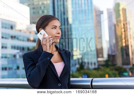 Asian woman calling on mobile phone in Vancouver city business district.