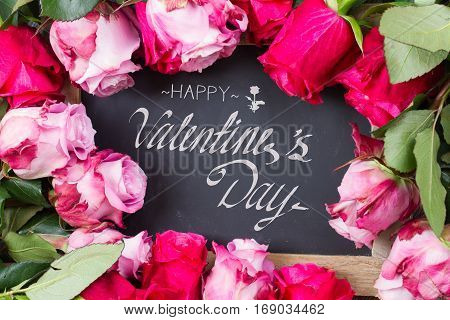 blooming dark and pink roses frame laying on table with happy valentines day greetings