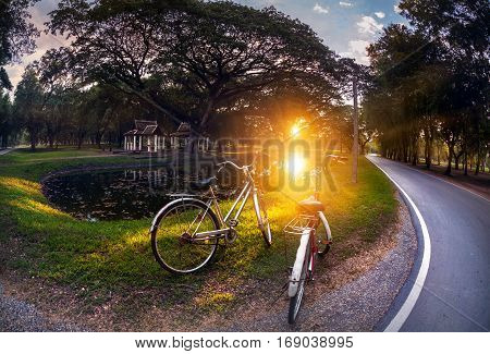 Two vintage bicycle near pond in the Sukhothai historical park at beautiful sunset in Thailand