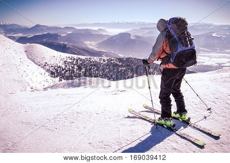 Man on skis in mountains, man alone in Alps skier in wild, skialpinist on mountain, symbol of sporting activities