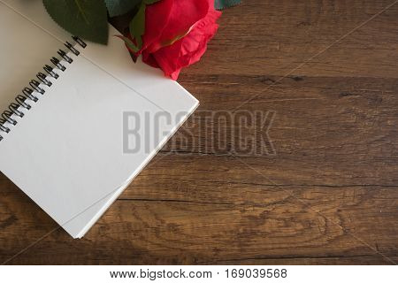 blank note book on wooden table with artificial red roses for romance memories written concept.