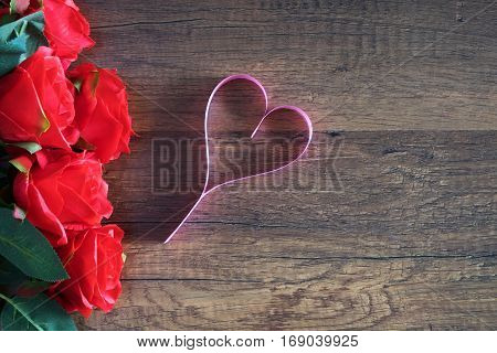 heart make from pink ribbin near a bloom red roses on wooden table for anniversary; valentine; congratulation; tell to love concept