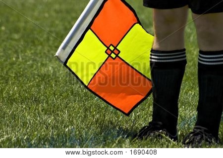Soccer Referee With A Yellow And Orange Flag