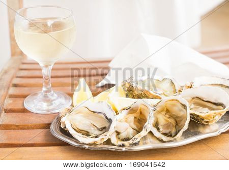 Raw oysters shells plate and glass of white wine