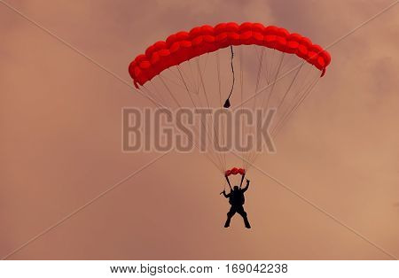 Male parachutist makes the jump from the plane on a red parachute.