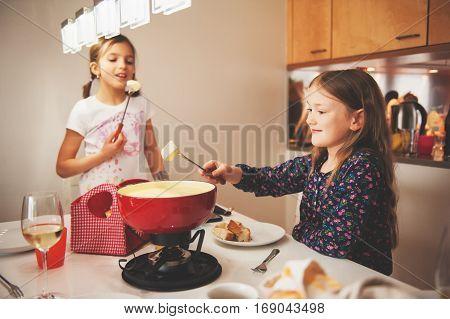 Two kid girls eating swiss  fondue for dinner