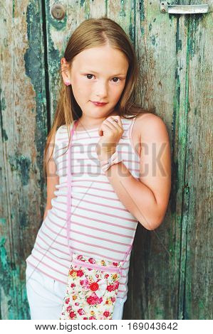 Vertical portrait of a cute little 7-8 year old girl wearing many accessories