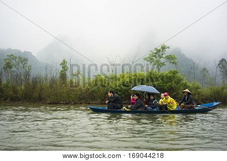 Hanoi, Vietnam - Feb 23, 2014: Tourists on rowing boat on the way to Huong pagoda in festival season by new year time