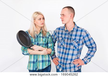 Man and woman quarrel. A woman with a frying pan in his hands. Humorous concept of a family quarrel.